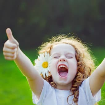 Laughing girl showing thumbs up