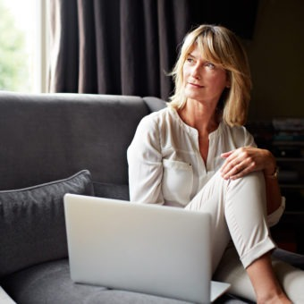 woman sitting on her sofa using a laptop